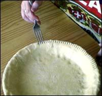 Crimping the dough edges with a fork