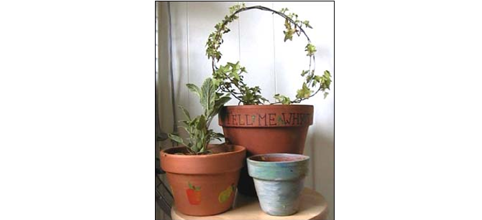 """The ivy pot has """"Tell me why the ivy twines"""" written in Sharpie pen, with freehand leaves; the sage pot was rubber-stamped and then touched up; and the little pot was the result of Josie slopping on paint and Mommy brushing it out for her--turned out rather Monet-like!"""
